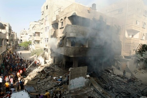 Palestinians gather around a house which police said was hit in an Israeli air strike, in Gaza City