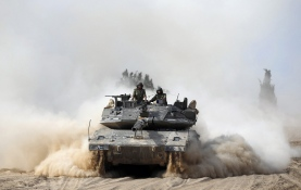 Israeli soldiers ride atop a tank outside the southern Gaza Strip