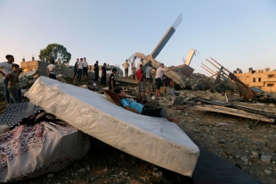 A Palestinian boy rests on a mattress next to the rubble of a house which police said was destroyed in an Israeli air strike in Gaza City